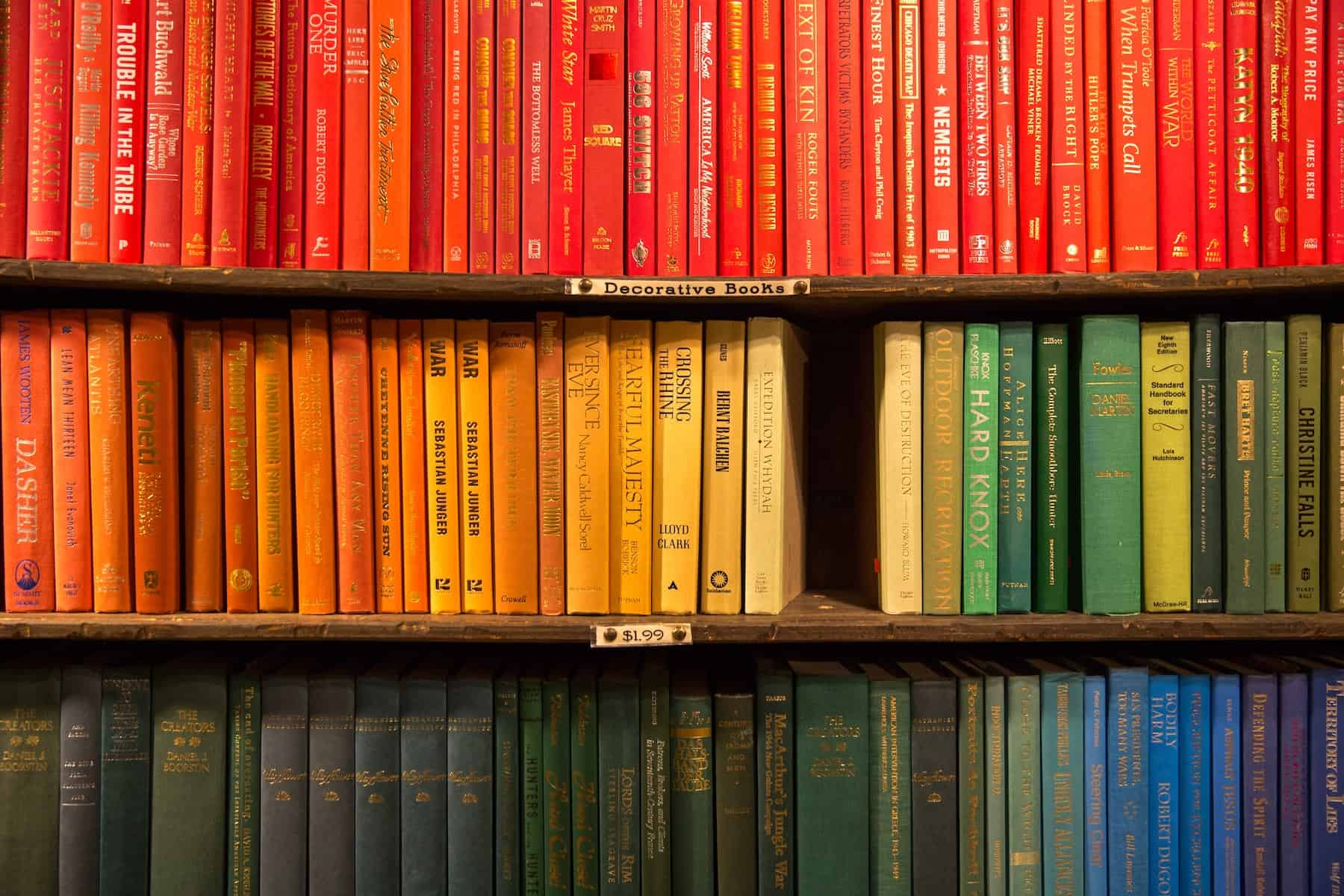 Three shelves of a library, showing books arranged by color of the spine. The top shelf is red books, the middle shelf is orange to green, the bottom shelf is dark green.
