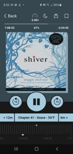 An audiobook screen, showing the book cover of Shiver by Maggie Stiefvater, plus the audiobook controls, including the play button, skip forward/backward buttons, controls for the speed, sleep timer, and the bookmark button..