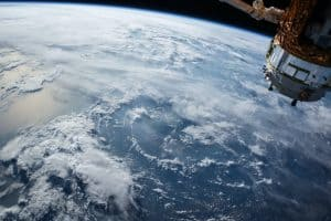 A photo of the earth from space, featuring a small part of a spaceship in the foreground.