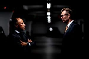 Two men in business suits staring at each other in a dark parking lot. One has his arms crossed and looks angry.